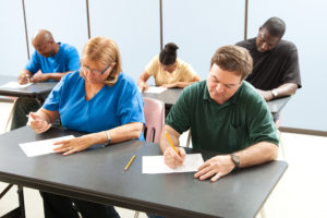 Classroom of adult education students taking a test in school