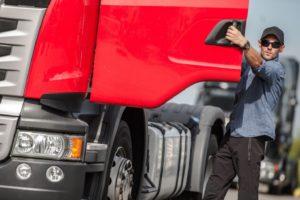 man next to semi truck with door open